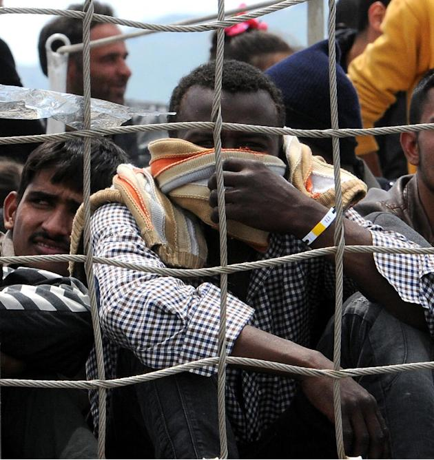 FILE - In this May 30, 2015 file photo, migrants wait to disembark from the Irish naval ship Le Eithne in the harbor of Palermo, Italy. The Italian coast guard says it has coordinated the rescue of mo