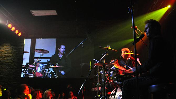 This march 26, 2013 photo shows Night Ranger drummer Kelly Keagy, right, and on the video screen, belting out a tune during a grand opening week concert at the Brennan Rock & Roll Academy in Sioux Falls, S.D. The center will give Boys & Girls Clubs members a chance to learn guitar, bass, drums, keyboards and vocals. (AP Photo/Dirk Lammers)