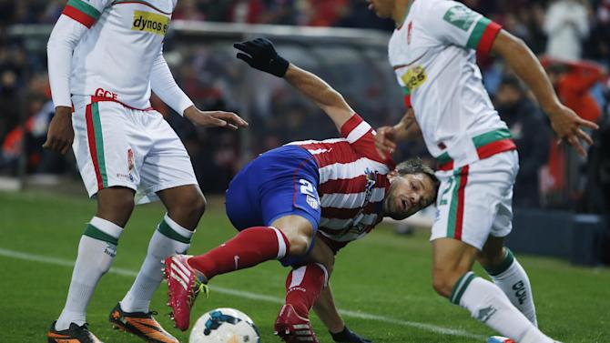 Atletico's Diego Ribas, centre, competes with Granda players during a Spanish La Liga soccer match between Atletico Madrid and Granada at the Vicente Calderon stadium in Madrid, Spain, Wednesday, March 26, 2014