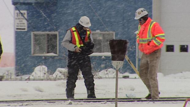 Rail workers investigate a section of track after three contractors were hit while clearing snow east of Edmonton on Boxing Day.