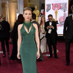 """FILE - In this Feb. 22, 2015 file photo, actress Scarlett Johansson arrives at the Dolby Theatre in Los Angeles. Johansson is defending John Travolta and calls the image of him kissing her on the Academy Awards red carpet """"an unfortunate still-frame from a live-action encounter that was totally sweet and totally welcome."""" Travolta greeted Johansson at Sunday's Oscars with a kiss and his arm around her waist. The photo has since been turned into an Internet meme. (Photo by Chris Pizzello/Invision/AP, File)"""