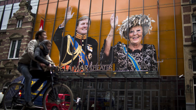 A cyclists passes by an image of Dutch Queen Beatrix and her son Crown Prince Willem-Alexander on the exterior of a theater  in downtown Amsterdam, Netherlands Monday, April 29, 2013. Queen Beatrix has announced she will relinquish the crown on April 30, 2013, after 33 years of reign, leaving the monarchy to her son Crown Prince Willem Alexander. (AP Photo/Emilio Morenatti)