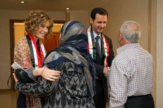 This photo taken on March 20, 2014, posted on the official Facebook page of the Syrian Presidency, shows first lady Asma Assad, left background, and Syrian President Bashar Assad, right background, shaking hands with Syrian teachers in Damascus, Syria. As Syrian army made gains on the battlefield, Assad's Britain-born wife has come out of seclusion, joining her husband's campaign to infuse confidence and optimism into the war-wrecked nation. Since January, Asma Assad has made several carefully scripted public appearances in the past months. (AP Photo/Syrian Presidency via Facebook)