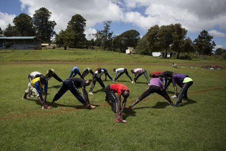 Athletes stretch during a training session on the training grounds in the town of Iten in western Kenya