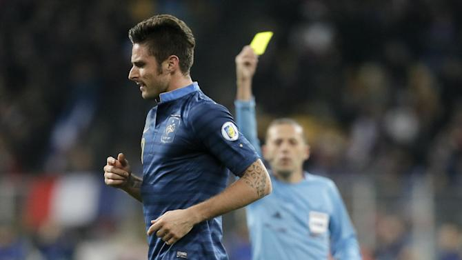 France's Olivier Giroud is shown a yellow card by referee Cuneyt Cakir from Turkey during the World Cup qualifying playoff first leg soccer match against Ukraine at the Olympiyskiy national stadium in Kiev, Ukraine, Friday, Nov. 15, 2013