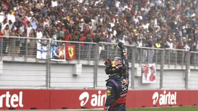 Red Bull Formula One driver Vettel celebrates atop his car after winning the Indian F1 Grand Prix at the Buddh International Circuit in Greater Noida