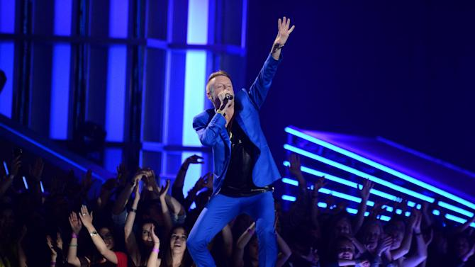 FILE - This April 14, 2013 file photo provided by MTV shows rapper Macklemore of Macklemore & Ryan Lewis, performing at the MTV Movie Awards in Sony Pictures Studio Lot in Culver City, Calif. MTV announced Wednesday, July 17, 2013, that Justin Timberlake and Macklemore & Ryan Lewis have six MTV Video Music Award nominations each. Bruno Mars has four nominations. (AP Photo/ MTV, Jordan Strauss, File)