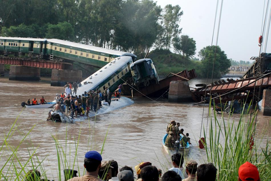 Pakistan Army soldiers and rescue workers gather at the site after a train fell in a canal near Gujranwala