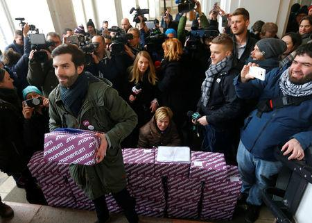 A leader of political movement Momentum Fekete-Gyor holds one of the boxes consisting over 266,000 signatures from Budapest voters who want a referendum on Budapest's bid to host the 2024 Summer Olympics in Budapest