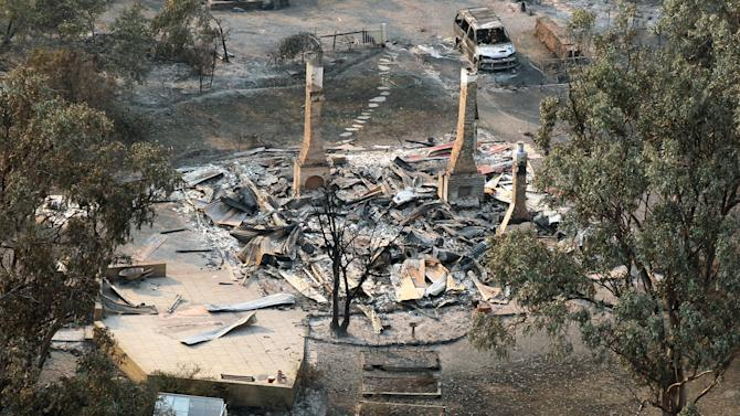 A charred vehicle sits near the remains of a destroyed home following a wildfire near Dunalley, east of the Tasmanian capital of Hobart, Australia, Saturday, Jan. 5, 2013.  Australian officials battled a series of wildfires amid scorching temperatures across the country on Saturday, with one blaze destroying dozens of homes in the island state of Tasmania. (AP Photo/Chris Kidd, Pool)