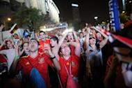 Supporters of the Spanish national football team react as they watch the Euro 2012 Championships football match between Spain and Portugal on a giant screen near the Santiago Bernabeu Stadium in Madrid. Defending champions Spain beat Portugal 4-2 on penalties after their Euro 2012 semi-final finished 0-0 after extra-time