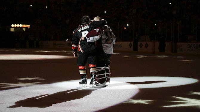 Anaheim Ducks' Teemu Selanne, left, of Finland, and Colorado Avalanche goalie Jean-Sebastien Giguere, who plan to retire after the season, hug as they are honored after an NHL hockey game on Sunday, April 13, 2014, in Anaheim, Calif. The Ducks won 3-2 in overtime