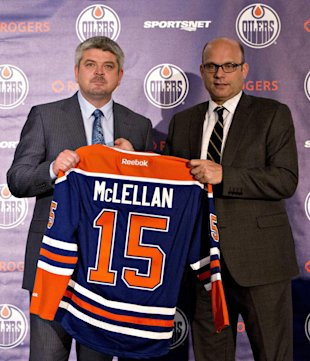 Todd McLellan, left, and Peter Chiarelli, President of Hockey Operations and General Manager of the Edmonton Oilers, hold up a jersey during a news conference after the Oilers announced McLellan as their new head coach, Tuesday, May 19, 2015 in Edmonton, Alberta. (Jason Franson/The Canadian Press via AP) MANDATORY CREDIT