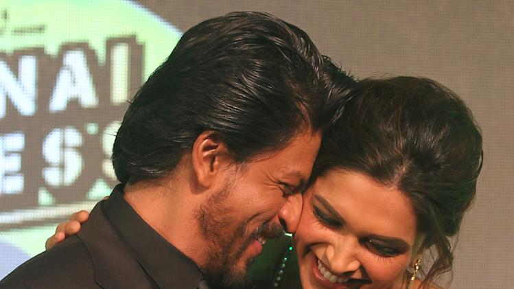 "Bollywood star Shah Rukh Khan, left shares light moment with co actor Deepika Padukone during the music release his upcoming movie ""Chennai Express"" in Mumbai, India, Wednesday, July 3, 2013. Directed by Rohit Shetty, the film scheduled for release on August 8 features Khan and Padukone in lead roles. (AP Photo/Rafiq Maqbool)"