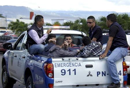 Policemen escort five Syrian men after they were detained at Toncontin international airport in Tegucigalpa