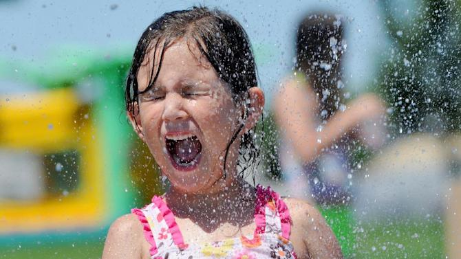 Kayla Holdridge, 6, of Eagle, is sprayed with water at Settlers Park Friday, June 28, 2013 in Meridian, Idaho. Many people looked for ways to beat the heat as temperatures in the Treasure Valley soared into the triple digits. (AP Photo/The Idaho Press-Tribune, Adam Eschbach) MANDATORY CREDIT