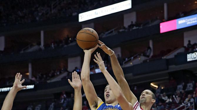 Golden State Warriors' Klay Thompson (11) has his shot tipped by Houston Rockets' Francisco Garcia (32) as Omri Casspi (18) defends during the first quarter of an NBA basketball game Friday, Dec. 6, 2013, in Houston