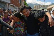 Ivan Vasquez (C), the only survivor of his family, killed by an earthquake, is helped during their burial, in San Cristobal Cucho municipality, in San Marcos, 260 km from Guatemala City, on November 9. Some 16,000 people were affected by the 7.4 magnitude quake off Guatemala's Pacific coast on Wednesday, which was this country's most violent seismic event since 1976