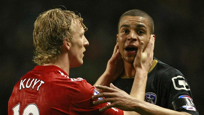 Oldham Athletic's Tom Adeyemi is calmed by Liverpool's Dirk Kuyt during their FA Cup third round soccer match at Anfield, Liverpool, England, Friday Jan. 6, 2012. The police are investigating an incident in which a black Oldham player appeared to be the target of abuse from Liverpool fans during an FA Cup third-round match on Friday. Oldham right back Tom Adeyemi was visibly upset late in the game at Anfield after seemingly taking offence from something shouted from the Liverpool-supporting area known as The Kop.  (AP Photo/Tim Hales)