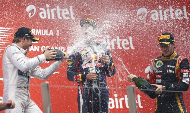 Mercedes Formula One driver Rosberg and Lotus F1 Formula One driver Grosjean spray champagne on the face of Red Bull Formula One driver Vettel on the podium after the Indian F1 Grand Prix at the Buddh