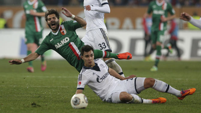 Augsburg's Halil Altintop of Turkey, top, is fouled by Schalke's Kaan Ayhan of Turkey challenge for the ball during the German first division Bundesliga soccer match between FC Augsburg and FC Schalke 04, in Augsburg, southern Germany, Friday, March 14, 2014