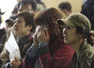 A mother weeps as she and others search for their children's names among a list of survivors rescued from a ferry that sank off the country's southern coast, at Danwon high school in Ansan, South Korea, Wednesday, April 16, 2014. Dozens of boats, helicopters and divers scrambled to rescue more than 470 people, including 325 students on a school trip from the high school, after the ship sank earlier in the day. (AP Photo/Ahn Young-joon)