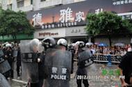 A July 2 photo released by rights watchdog China Human Rights Defenders allegedly shows Chinese riot police (left) on guard along a street in the small city of Shifang. Police stood guard over hundreds of people gathered in a tense Chinese city Wednesday, a day after authorities bowed to violent protests and cancelled plans to build a controversial factory