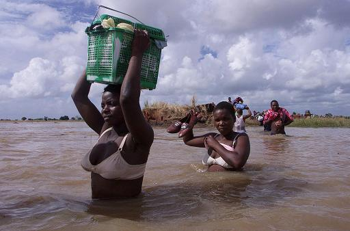 Mozambican women cross a flooded area close to the town of Palmeira, some 150 kilometers north of Maputo, in 2000