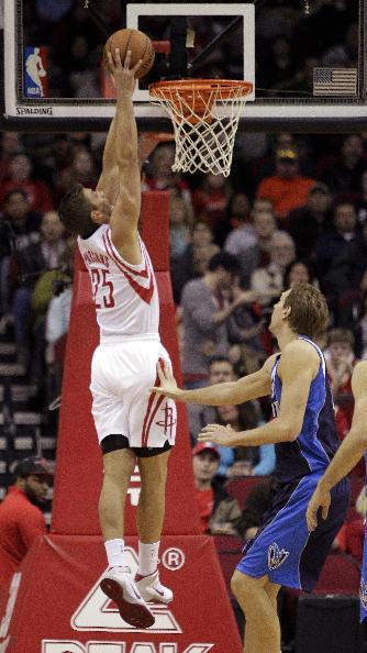 Houston Rockets small forward Chandler Parsons (25) drives for a dunk over Dallas Mavericks forward Dirk Nowitzki (41), of Germany, during the first half of an NBA basketball game, Monday, Dec. 23, 2013, in Houston