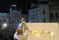 A man places a candle on top of a white board set up to place messages for passengers onboard the missing Malaysia Airlines Flight MH370 during a candlelight vigil in Kuala Lumpur April 6, 2014. REUTERS/Samsul Said