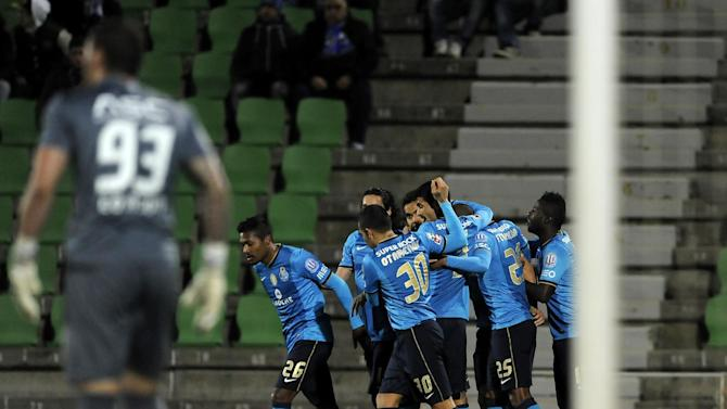 FC Porto's Maicon Roque, from Brazil, is mobbed by teammates after scoring the opening goal past Rio Ave's goalkeeper Ederson Moraes, from Brazil, in a Portuguese League soccer match, in Vila do Conde, northern Portugal, Sunday, Dec. 15, 2013