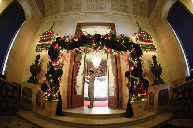 AYLESBURY, ENGLAND - NOVEMBER 16: A National Trust employee adjusts the Christmas decorations in the Main Entrance of Waddesdon Manor on November 16, 2012 in Aylesbury, England. The East Wing and Bachelor's Wing of Waddesdon Manor have been elaborately decorated for Christmas in the theme of English traditions and literature. The light-artist Bruce Munro has also created two installations in the grounds of the manor. The Christmas decorations at Waddesdon Manor are open to the general public until January 1, 2013. (Photo by Oli Scarff/Getty Images)