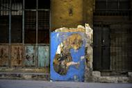 In this Feb. 12, 2017 photo, work of urban artist Yulier P. adorns a wall on a street in Havana, Cuba. The canvas of the The 27-year-old artist, whose full name is Yulier Rodríguez, consists of walls, usually rough, peeling, on buildings or houses that seem to be collapsing or have been abandoned. (AP Photo/Ramon Espinosa)
