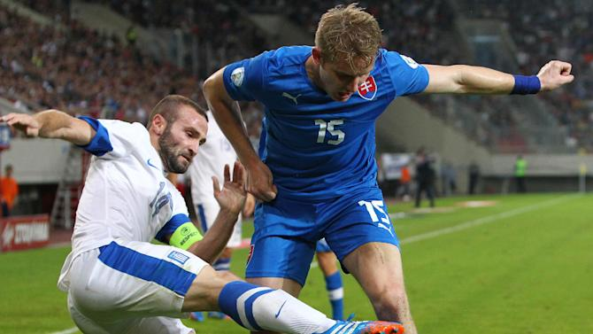 Greece's Dimitris Salpigidis, left, fights for the ball with Slovakia's Tomas Hubocan during their World Cup Group G qualifying soccer match at the Karaiskaki stadium in the port of Piraeus, near Athens, Friday, Oct. 11, 2013