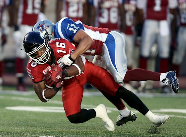 Calgary Stampeders' Marquay McDaniel is tackled by Montreal Alouettes' Chip Cox during the first half of their CFL football game in Montreal