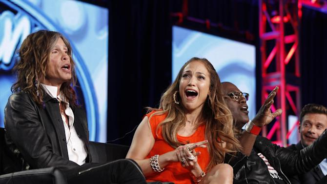 """FILE - In this Jan. 8, 2012 photo, """"American Idol"""" judge Jennifer Lopez, center, reacts as fellow judge Steven Tyler, left, of Aerosmith makes a joke about wearing Lopez's pants as Randy Jackson and Ryan Seacrest are seen at right during the """"American Idol"""" panel at the Fox Broadcasting Company Television Critics Association Winter Press Tour in Pasadena, Calif. """"American Idol"""" is on the brink of a crisis, Thursday, July 12, 2012, as judge Steven Tyler is leaving, and fellow judge Jennifer Lopez is dithering about staying put. (AP Photo/Danny Moloshok, File)"""