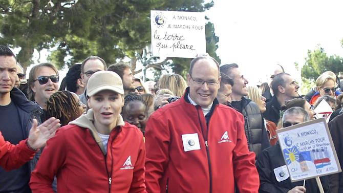 Prince Albert II of Monaco with his wife Princess Charlene and their twins, Prince Jacques, right, and Princess Gabriella, take part in the World Climate March in Monaco, Sunday, Nov. 29, 2015. This march takes place ahead of the Conference of Parties to the United Nations Framework Convention on Climate Change (COP 21), in Paris, France. (AP Photo/Lionel Cironneau)
