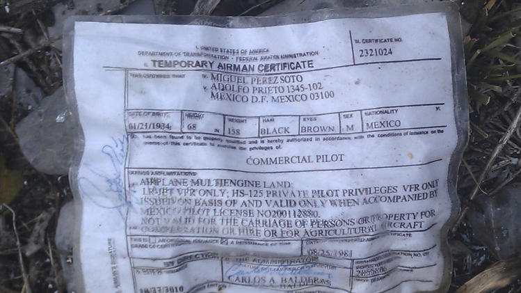 A temporary airman's certificate issued by the Federal Aviation Administration (FAA) sits on the ground at the crash site where a plane carrying U.S. born singer Jenni Rivera apparently crashed near Iturbide, Mexico Sunday Dec. 12, 2012. The wreckage of a small plane believed to be carrying Rivera, the singer whose soulful voice and unfettered discussion of a series of personal travails made her a Mexican-American superstar, was found in northern Mexico on Sunday. Authorities said there were no survivors. (AP Photo)