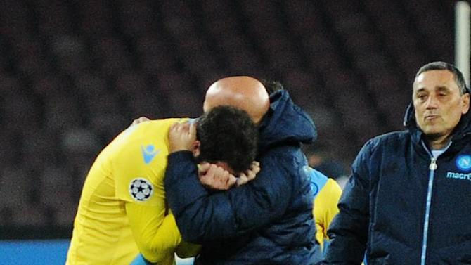 Napoli's Gonzalo Higuain is comforted by a team staffer as he walks off the pitch at the end of a Champions League, group F, soccer match between Napoli and Arsenal, at the Naples San Paolo stadium, Italy, Wednesday, Dec. 11, 2013. Ten-man Arsenal advanced to the Champions League knockout phase for the 14th consecutive year despite a 2-0 loss Wednesday at Napoli, which was eliminated. Gonzalo Higuain scored in the 73rd minute but the San Paolo stadium was soon silenced when word arrived that Borussia Dortmund had scored a late goal in a 2-1 win at Marseille to win Group F