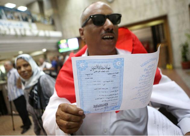 FILE - In this Sept. 4, 2014 file photo, Adel Mohammed Ahmed, wearing a national flag, holds an investment certificate used to finance the extension of the Suez Canal at the National bank, in Cairo, E