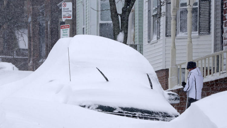 A woman shovels out a car on Third street in the South Boston neighborhood of Boston on Saturday, Feb. 9, 2013. A behemoth storm packing hurricane-force wind gusts and blizzard conditions swept through the Northeast overnight. (AP Photo/Gene J. Puskar)