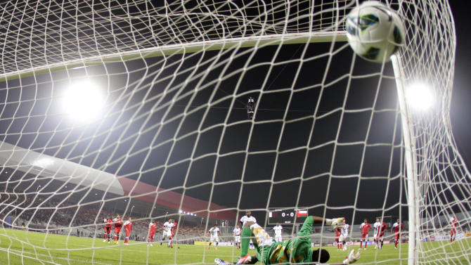 Qatar's Ibrahim scores first goal in penalty kick against Oman during Gulf Cup Tournament soccer match in Isa Town