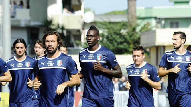 Italy's Mario Balotelli, center,  and Andrea Pirlo lead the group  during a training session with their team at the Giarrusso stadium in the outskirts of Naples, Monday, Oct. 14, 2013, ahead of a 2014 FIFA World Cup, Group B, qualification match against Armenia in Naples on Tuesday.  Other teams in Group B are, Denmark, Bulgaria, Czech Republic, and Malta