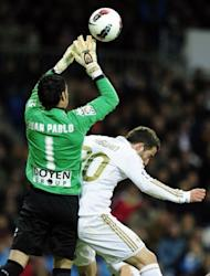Sporting Gijon's goalkeeper Juan Pablo (L) clashes with Real Madrid's forward Gonzalo Higuain during their Spanish La Liga match at the Santiago Barnabeu stadium in Madrid. Real Madrid came from behind to win the match 3-1