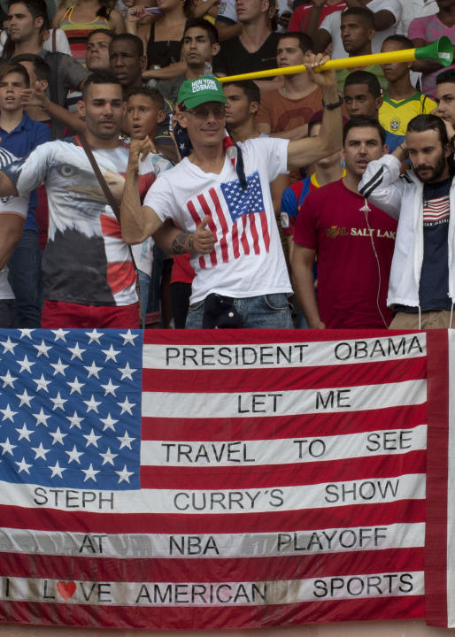 """Cuban soccer fans stand next to a United States flag that reads """"President Obama let me travel to see Steph Curry's show at NBA Playoff, I love American Sports,"""" during friendly soccer m"""