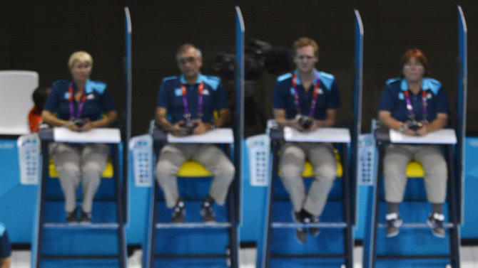 Judges watch as China's He Chong performs a dive during the men's 3m springboard preliminary round at the London 2012 Olympic Games at the Aquatics Centre