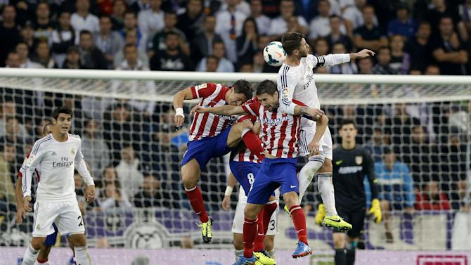 Real Madrid's Sergio Ramos, right, jumps for the ball with Atletico de Madrid's Gabi Fernandez, second from right, Raul Garcia (8), center, and Cristian Rodriguez from Uruguay, third from right, as Real Madrid's Alvaro Morata, left, watches, during a Spanish La Liga soccer match at the Santiago Bernabeu stadium in Madrid, Spain, Saturday, Sept. 28, 2013