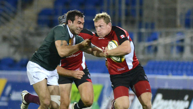 The Australian Barbarian's Rod Davies, left, tackles Canada's Phil Mackenzie during their rugby union match on the Gold Coast, Australia, Friday, Aug. 26, 2011. (AP Photo/Steve Holland)