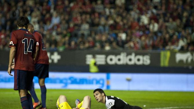 FC Barcelona's Lionel Messi of Argentina, on the pitch laments beside goalkeeper Andres Fernandez, right, during their Spanish League soccer match, at El Sadar stadium, in Pamplona northern Spain on Saturday, Oct. 19, 2013