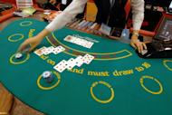 This file photo shows a dealer handing out cards during an exhibit on the gaming industry, in Manila, on March 22, 2007. A $4 billion mega-casino complex is set to open in the Philippines in mid-March when the first of four franchise-holders starts commercial operations, the parent firm said in a disclosure released on Wednesday